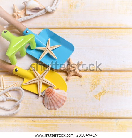 Tools for kids for playing in sand and sea object on  yellow  painted wooden background. Place for text. Vacation background. Square image. - stock photo