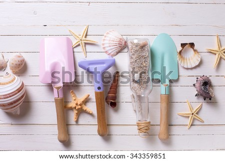 Tools for kids for playing in sand and sea objects on white  painted wooden background. Place for text. Vacation background. - stock photo