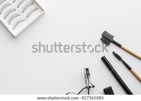 Tools for make-up in the corners of the shot with the place for lettering in the center of the photo. White background. Standard set for eyes in beauty salons. - stock photo
