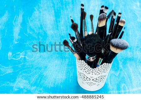 Tools for makeup and cosmetics different shades of lipstick on blue wooden background