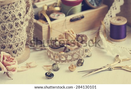 Tools for needlework, thread for sewing, scissors, buttons and vintage laces. Toned image