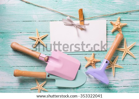 Tools for playing in san,  sea objects and empty tag  on turquoise  painted wooden planks. Place for text. Vacation, holiday, summer background. - stock photo