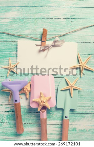 Tools for playing in sand  and sea object on turquoise  painted wooden planks. Place for text. Vacation, holiday, summer background. Toned image. - stock photo