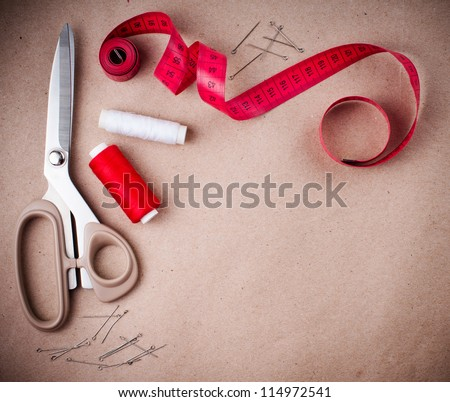 Tools for sewing and handmade: thread, scissors, pins on brown paper. - stock photo