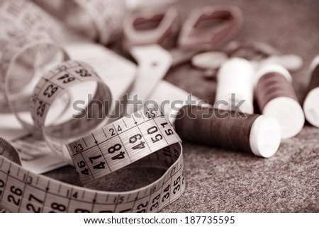 Tools for sewing:  thread,  buttons,  scissors, tape in brown tone