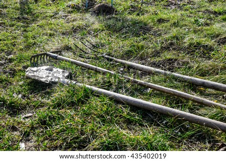 tools for working on the land: a shovel , a rake - stock photo