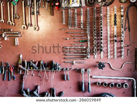 Tools hanging on a wooden clipboard, hobby time in garage. - stock photo