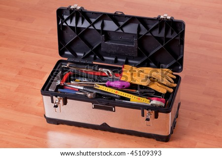 tools in tool box on wooden floor - stock photo