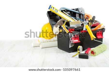 Tools in toolbox over wooden floor against empty wall. Copy space. - stock photo