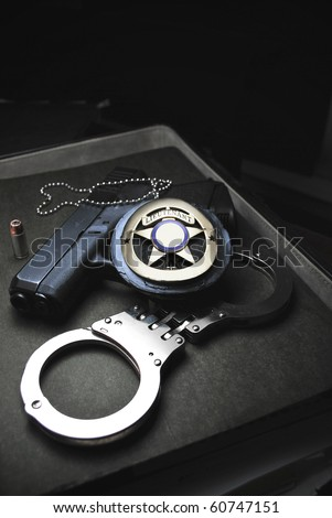 Tools of the trade in Law Enforcement, badge, handcuffs, and firearm/Protect & Serve - stock photo