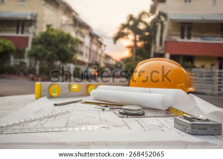 Tools on architect blueprints with house - stock photo