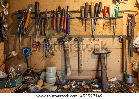 Tools on the wall and table to keep hammers, wrenches, ring spanners, hammer, pliers, screwdrivers, screws, bolts, adjustable wrench,  insulating tape and other do-it-yourself (DIY) tools - stock photo