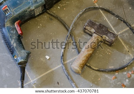 Tools Supplies. Metal sledge hammer on tiled floor with rubble of concrete and tiles. Sledge hammer old and rusty - stock photo