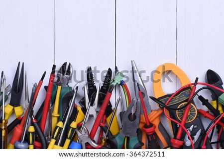 Tools to use in electrical installations on wooden background - stock photo