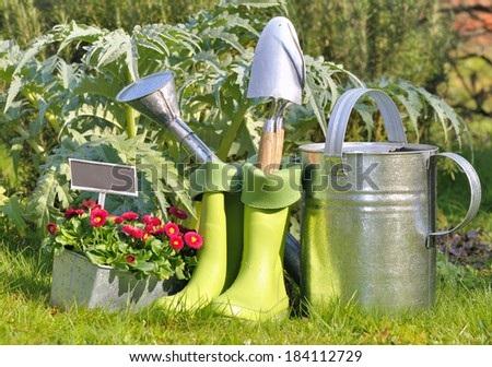 tools, watering can and gardening boots in the garden - stock photo