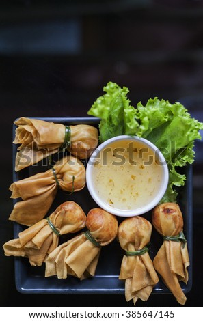 Toong thong,Thai food, oriental deep fried wontons filled with prawn and spring onion, served with dumpling and sauces - stock photo
