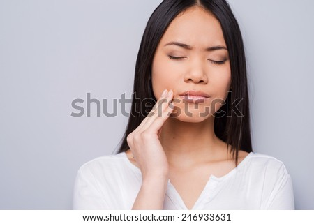 Toothache. Beautiful young Asian women touching her cheek and keeping eyes closed while standing against grey background  - stock photo