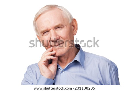 Toothache. Frustrated senior man in shirt holding hand on his cheek and keeping eyes closed while standing against white background - stock photo