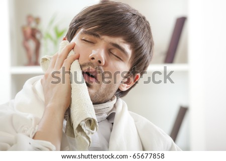 toothache - sick man covering with towel his cheek - stock photo