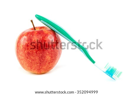 Toothbrush and fresh red apple isolated on white background.