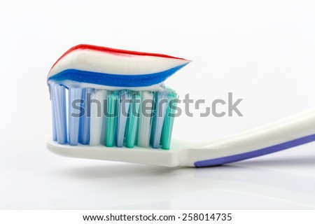 Toothbrush and toothpaste on white background