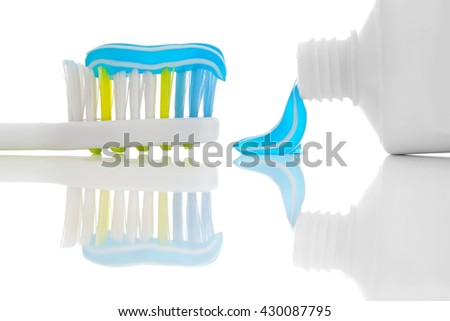 Toothbrush and toothpaste placed on a glossy surface. - stock photo