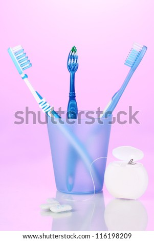 Toothbrush in glass, dental floss and chewing gum on purple background - stock photo