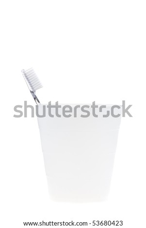 Toothbrush in toothbrush tumbler isolated on white background - stock photo