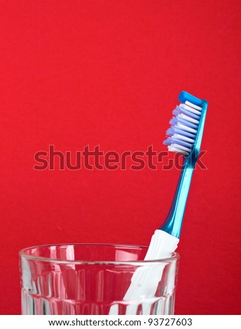 Toothbrush in transparent glass against red background - stock photo
