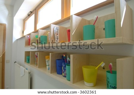 toothbrush tumbler, toothbrush and toothpaste on a wooden rack