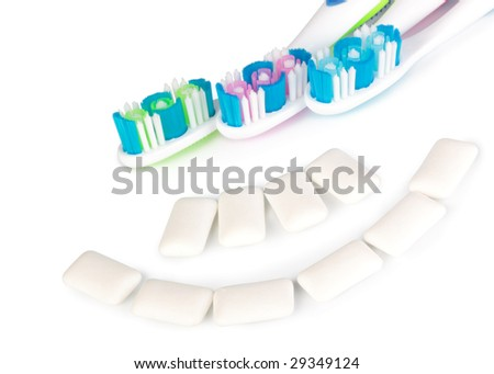 Toothbrushes and chewing gum on a white background
