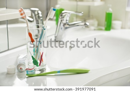 Toothbrushes and toothpaste in the bathroom close up.