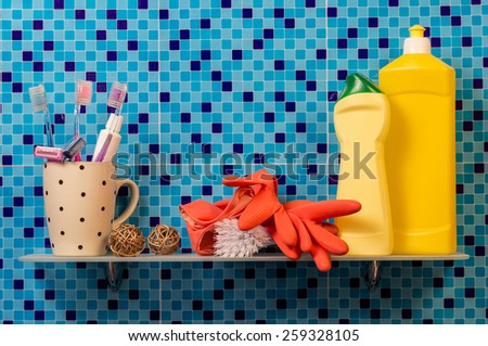 Toothbrushes in a cup, rubber gloves and cleaning products on the shelf - stock photo