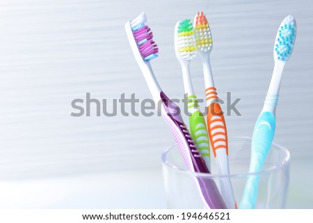 Toothbrushes in glass on table on light background - stock photo