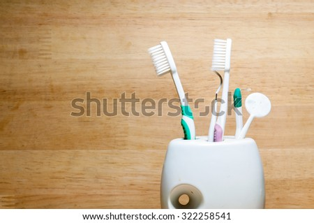 toothbrushes in glass on wooden texture - stock photo