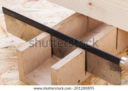 Toothed steel hand saw cutting through a new beam of wood left in position surrounded by wood chips with nobody in the frame in a DIY, carpentry, woodworking or joinery concept - stock photo