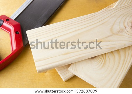 Toothed steel hand saw cutting through a new boards of wood surrounded by wood chips with nobody in the frame in a DIY, carpentry, woodworking or joinery concept - stock photo