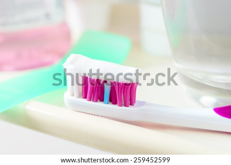 Toothpaste on toothbrush ready for teeth cleaning - stock photo