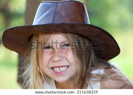 Toothy smile of young pretty girl in cowboy hat, facial portrait - stock photo