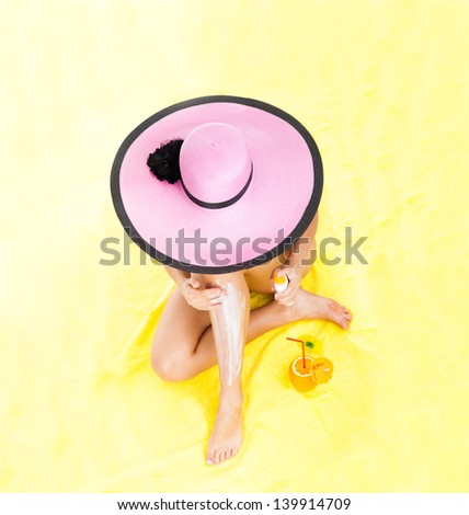 Top angle view above woman moisturizing applying sun cream on her tanned body legs, girl wear pink hat black swimsuit sitting on yellow sand towel with cocktail, beach travel vacation concept - stock photo