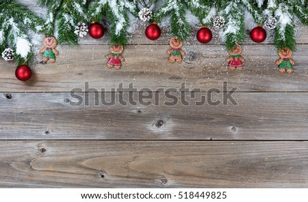 Top border of Christmas objects and snow on rustic wood for the holiday.