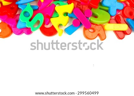 Top border of colorful toy magnetic letters and numbers over a white background - stock photo