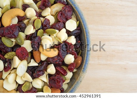 Top close view of a bowl full of an assortment of nuts and dried cranberries trail mix on a wood table top. - stock photo