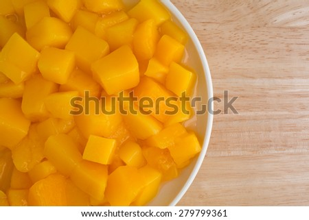 Top close view of a serving of canned diced mangoes in a small dish atop a wood table top. - stock photo