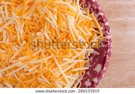 Top close view of a small colorful tray filled with shredded white cheddar, sharp cheddar and mild cheddar cheeses atop a wood table top. - stock photo