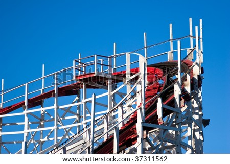 Top corner of roller coaster against solid blue sky