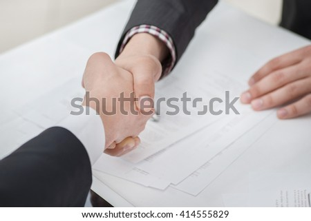 Top deal! Young businessmen shaking hands with each other in the business center. Successful businessmen on a corporate meeting close-up view - stock photo