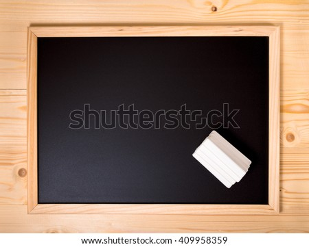 top down empty blank school black board with white chalks on wooden background, close up
