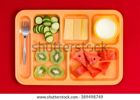 Top down perspective view on bright plastic child size lunch tray with fork, cucumber, cheese, kiwi, watermelon slices and little cup of milk - stock photo