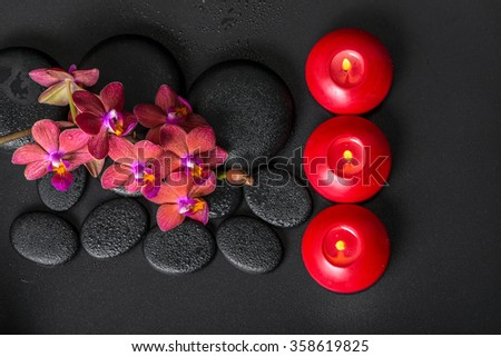 top down spa setting of blooming twig red orchid flower, phalaenopsis with water dew and candles on zen basalt stones - stock photo